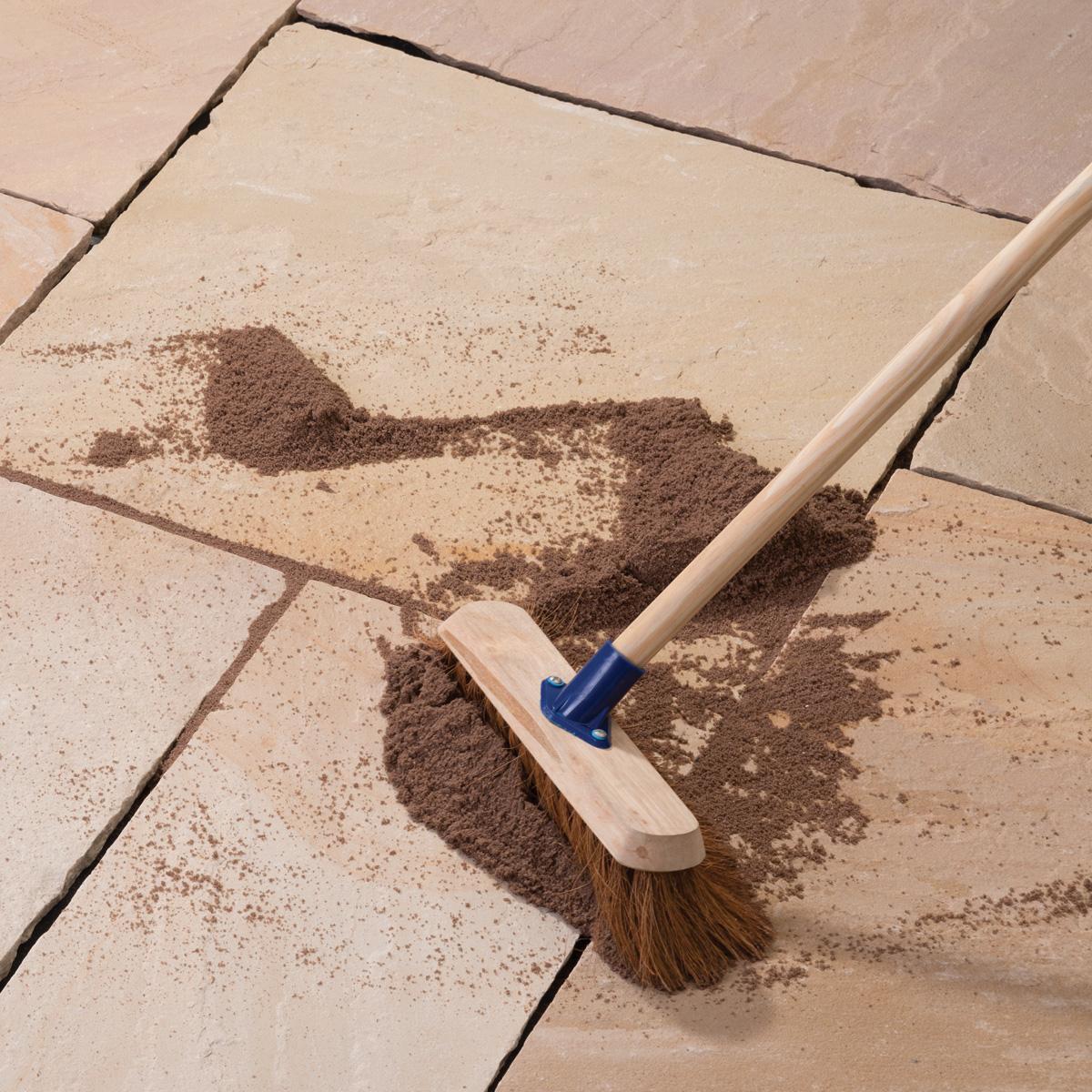 Brush into gaps between paving